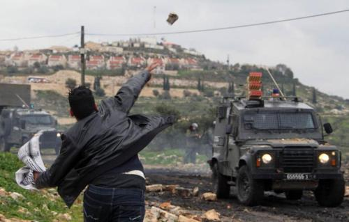 A Palestinian throws a rock towards armed Israeli soldiers in their armoured vehicle at a protest against the illegal expropriation of Palestinian land by Israel on 1 February 2013 in the village of Kafr Qaddum, near Nablus. (Photo: Jaafar Ashtiyeh - AFP)