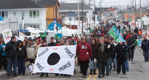 "Residents of Percé on the Gaspésie protest the EI reform. Their banner condemns the ""black hole"" seasonal workers suffer, the period when these workers are without an income from EI or their jobs."