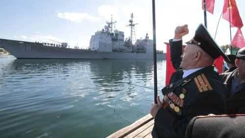 """Ukrainians protest """"visit"""" of USS Vella Gulf, a Ticonderoga class guided missile cruiser, at the Black Sea port of Sevastopol in January 2012. Their slogans included """"Yankee, go home!"""" and """"No to NATO!"""" The protesters also burned a U.S. flag featuring Nazi swastika instead of stars. Yevhen Dubovik, a protest organizer, said the visit of a ship with offensive weapons was illegal because it had not been authorized by Ukraine's parliament."""