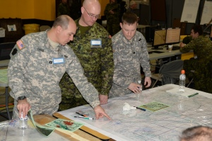 """Who's on first? """"Capt Rob Cuthie, Pennsylvania Army National Guard, points out the brigade's battle plan with WO Dan Covert, 2 Combat Engineer Regiment, and Capt Reed Preece. Pennsylvania Army National Guard, during Exercise UNIFIED RESOLVE 2014."""" 