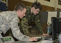 """Capt Reed Preece, Pennsylvania Army National Guard, and Cpl Nathan Richey, Royal Canadian Dragoons, work on the brigades battle plans during Exercise UNIFIED RESOLVE 2014 at CFB Petawawa. They are reading computer """"exif date"""" – """"a record of the settings a camera used to take a photo or video. This information is embedded into the files the camera saves, and we read and display it here.""""