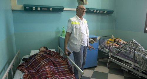 Dr. Basman al-'Ashi, Director of al-Wafa Hospital and two of the patients | Anne Pak, ActiveStills, 15 July 2014.