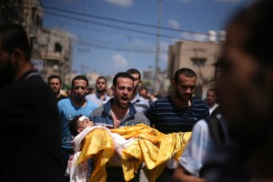 A relative carries the body of four-year-old Qassim Elwan during his funeral in Gaza City on 19 July. Qassim was killed along with his brother by Israeli shelling the previous day | Ezz al-Zanoun / APA images