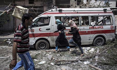 Two Palestinian girls run past a damaged ambulance in Gaza on Sunday, July 20 | Oliver Weiken/EPA