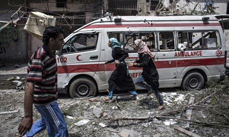 Two Palestinian girls run past a damaged ambulance in Gaza on Sunday, July 20 | Oliver Weiken/EPA
