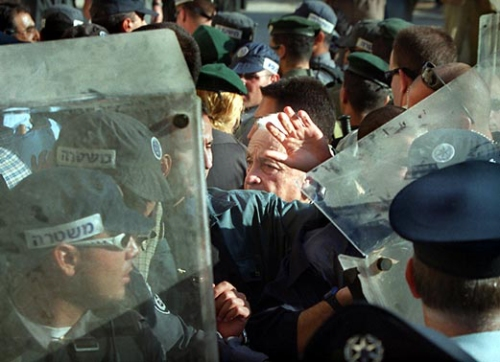 """On September 228, 2000 Ariel Sharon, then leader of the Likud opposittion, mde a provocative """"visit"""" to the Al=Aqsa Mosque, with thousnds of security forces deployed in and around the Old City of Jerusalem. Ensuing clashes with Palestinian protestors left in the first two days alone five Palestinians dead and over 200 injured. Sharon's """"visit' soon sparks a widespread uprising in the Occupied Territories, known as the the Second or Al-Aqsa Intifada. The aim of the provocation became known as advocating """"the strong hand"""" for """"the second half of 1948"""" (as Ya'alon, head of military intelligence puts it in November 2000) – to realize unfinished business, including killing the """"peace process"""" and finding another country for the Palestinian people. (Source: Dossier on Palestine, p. 59)"""