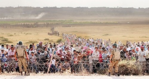 Turkish soldiers block Syrian refugees at border near Kobani. Turkey and the U.S. are cynically using the Kurdish people as a bargaining chip in a strategy of conquest