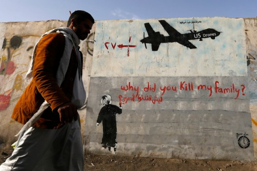 Man walks past a graffiti, denouncing strikes by U.S. drones in Yemen, painted on a wall in Sanaa