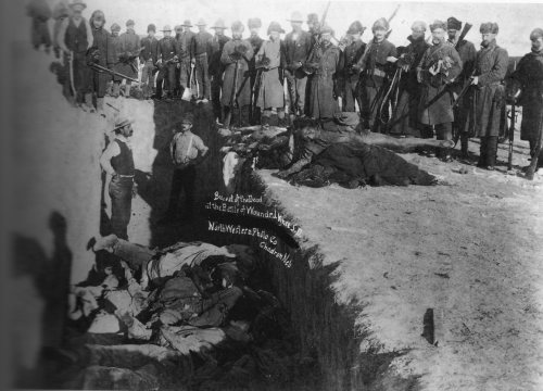 Heroic U.S. troops posing for a photo beside a mass grave dug for the victims of the massacre at Wounded Knee (Click to enlarge)