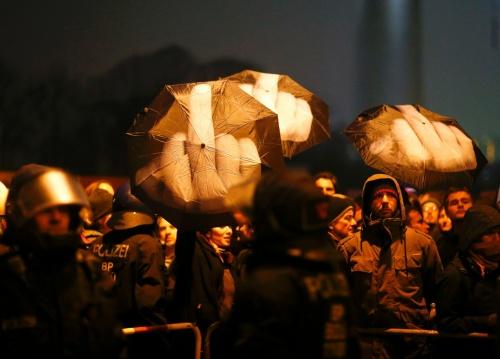 Demonstrators hold umbrellas as they protest in Berlin | Hannibal Hanschke/Reuters
