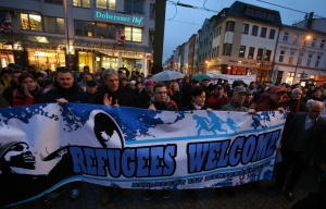 People hold a banner reading: 'Refugees welcome' as they take part in a protest against a rally by Pegida in Rostock, Germany | Bernd Wuestneck/AFP/Getty Images