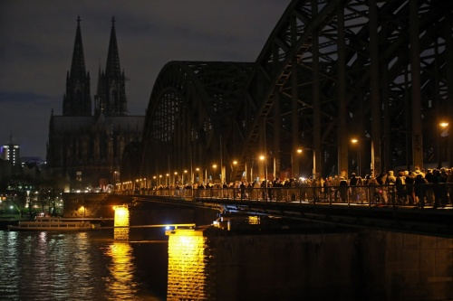 Cologne Cathedral's lighting is switched off to make a statement against racism as people cross the Hohenzollernbrücke bridge during protests | Oliver Berg/EPA
