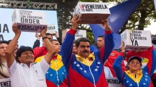Venezuelan President Nicolas Maduro (middle) holds aloft boxes of petitions signed by millions demanding U.S. President Obama withdraw sanctions.