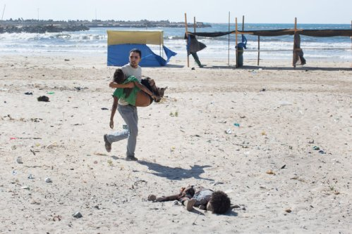 Civilians rushed to help after explosions hit a beach where children were playing in Gaza City. Four Palestinian boys died | Tyler Hicks/The New York Times
