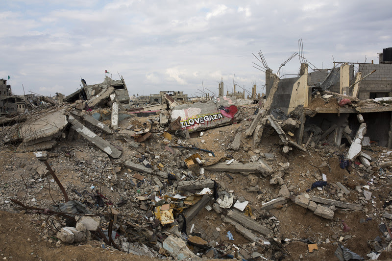 A graffiti is seen in one of the destroyed quarter of Shujayea, east of Gaza city, March 21, 2015. The rubble are then recycled to produce bad quality concrete. Six month after the ceasefire that ended the Israeli 2014 summer offensive, 100,000 Palestinians are still displaced and many live in dire conditions. Rebuilding materials are scarce as the Gaza Strip face restrictions imposed by Israel. Anne Paq ActiveStills