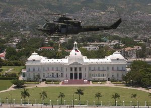 Canadian troops deployed in Port-au-Prince on the day of the coup; a Canadian military helicopter flies over the Presidential Palace as the coup unfolds.