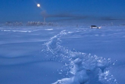 A car drives through the snow at night near Vostochnaya meteorological station.