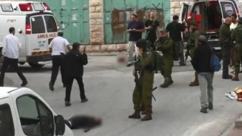 A screenshot from the video showing IDF soldiers and the subdued Palestinian | B'Tselem