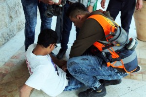 Medics rushed to one young man who was shot with a rubber-coated steel bullet in the leg | Abed al Qaisi/Mondoweiss)