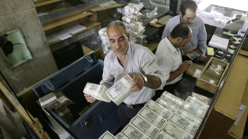 Banker stacks packed Syrian lira bills at the Central Bank in Damascus on Aug. 25, 2011 | Joseph Eid/AFP/Getty Images