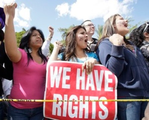From left to right, protesters Jennifer Luna, Jakleline Castro, and Mayvi Garcia, all of Phoenix, shout during a rally after the signing of immigration bill SB1070 into law by Gov. Jan Brewer Friday, April 23, 2010, in Phoenix. The sweeping measure would make it a crime under state law to be in the country illegally, and would require local law enforcement to question people about their immigration status if there is reason to suspect they are in the country illegally. (AP Photo/Ross D. Franklin)