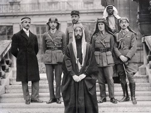 Feisal party at Versailles Conference. Left to right: Rustum Haidar, Nuri as-Said, Prince Faisal (front), Captain Pisani (rear), T. E. Lawrence, Faisal's slave (name unknown), Captain Hassan Khadri.
