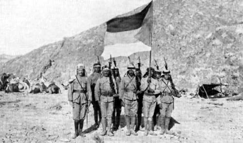 Soldiers in the Arab Army during the Arab Revolt of 1916-1918, carrying the Arab Flag of the Arab Revolt and pictured in the Arabian Desert.