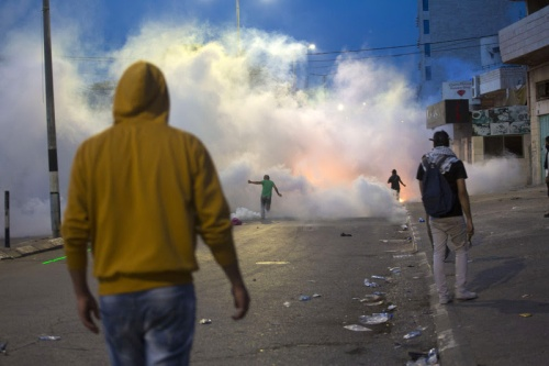 Palestinian protesters stand in a cloud of tear gas fired by Israeli forces during confrontations in the West Bank city of Bethlehem in October 2015   Anne Paq ActiveStills