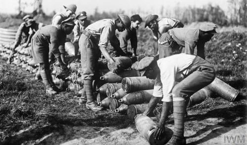 WEST INDIANS IN THE FIRST WORLD WAR (E(AUS) 2078) In action: West Indian troops stacking 8 inch shells at a dump on the Gordon Road, Ypres, October 1917. Copyright: © IWM. Original Source: http://www.iwm.org.uk/collections/item/object/205213105