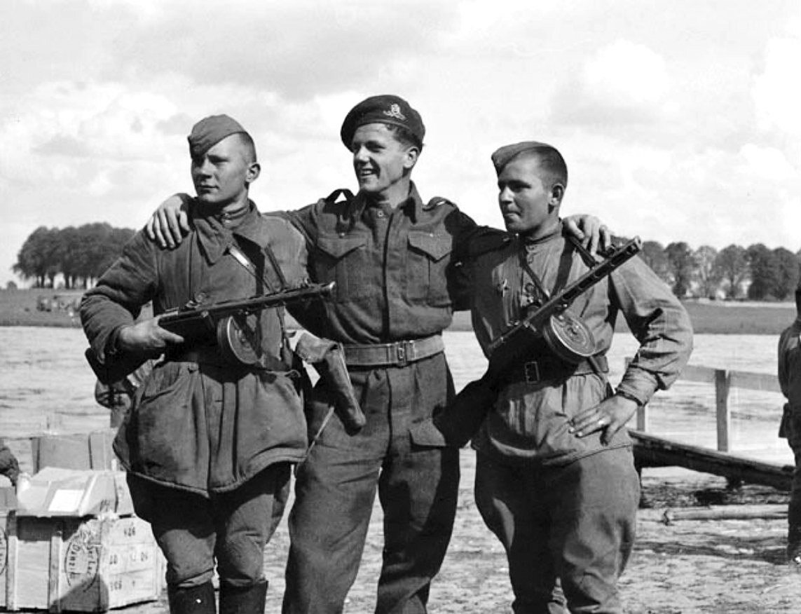A Canadian gunner from the Canadian Film and Photo Unit (center) with two soldiers at the Elbe river in Torgau, Germany on April 27, 1945, just two days after US and Soviet troops link-up.